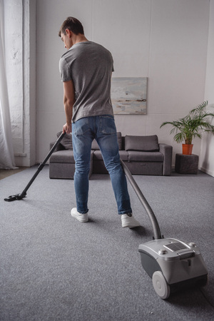 rear view of man cleaning carpet with vacuum cleaner in living room