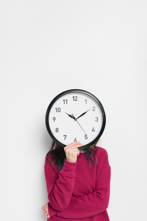 Woman holding clock over her face isolated on white