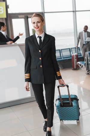 female pilot with suitcase walking by airport lobby 版權商用圖片