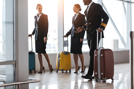 pilot and stewardesses with luggage walking by airport Stockfoto