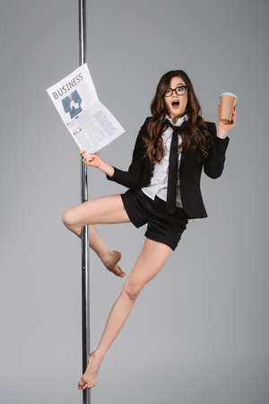 surprised young businesswoman in eyeglasses holding newspaper and paper cup, exercising with pole and looking at camera on grey Standard-Bild - 114251064