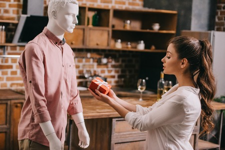 young woman pretending to except gift from mannikin, loneliness and perfect man dream concept Zdjęcie Seryjne