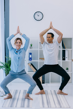businesswoman with her trainer practicing yoga at office