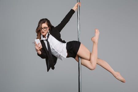 young businesswoman in eyeglasses using smartphone and exercising with pole on grey