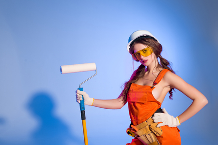 seductive girl in overalls and safety helmet with tool belt holding painting roller, on blue Foto de archivo