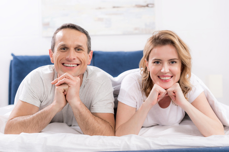 portrait of smiling wife and husband under blanket lying on bed at home Standard-Bild - 114324077