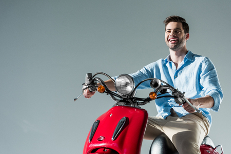 portrait of happy fashionable young man riding red scooter isolated on grey