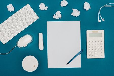 top view of blank sheet of paper with pen, calculator, computer mouse and keyboard on blue