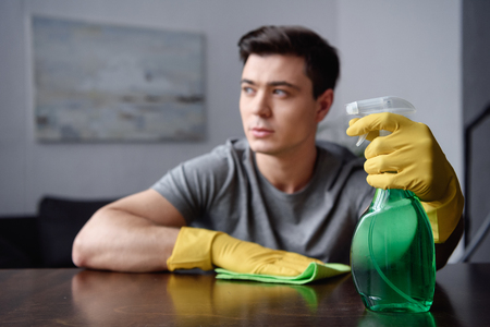 handsome man with spray bottle and rag looking away