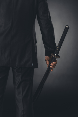 cropped shot of man in business suit with katana sword on black 写真素材