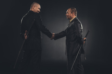 side view of businessmen shaking hands with katanas behind back isolated on black