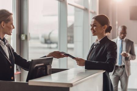 uśmiechnięta młoda bizneswoman dająca paszport i bilet personelowi przy stanowisku odprawy na lotnisku