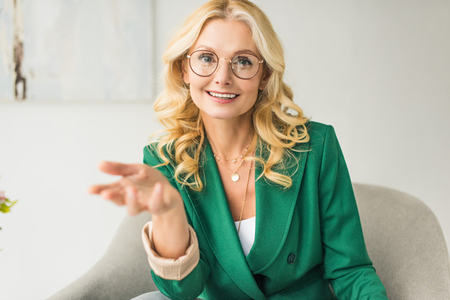 smiling middle aged businesswoman in eyeglasses looking at camera and gesturing with hand while sitting in armchair