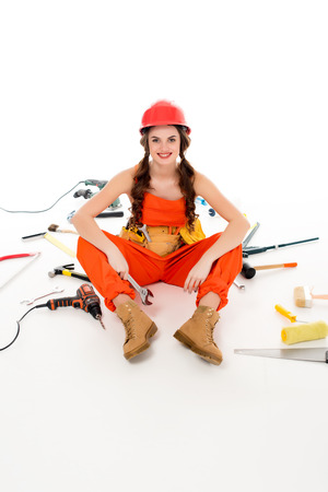 smiling girl in overalls and hardhat sitting on floor with different tools, isolated on white