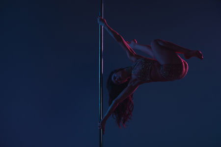 full length view of athletic flexible young woman dancing with pole on blue