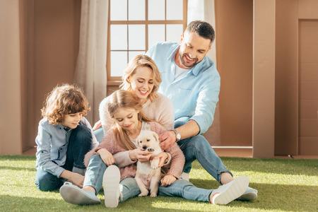 Hermosa joven familia con cachorro de laboratorio amarillo en el patio de la casa de cartón