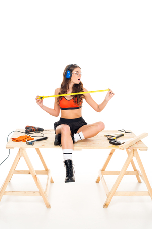 seductive girl in protective headphones sitting on wooden table with tools, isolated on white