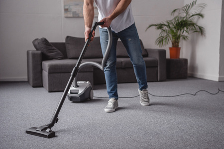 cropped image of man cleaning living room with vacuum cleaner
