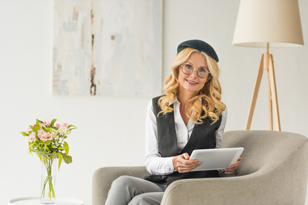 beautiful middle aged businesswoman in eyeglasses using digital tablet and smiling at camera