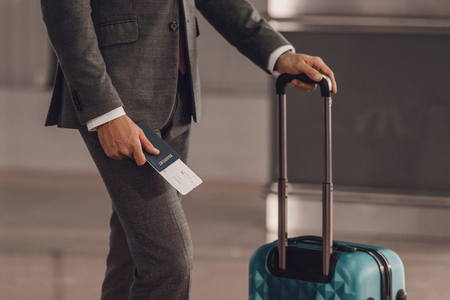 cropped shot of businessman with luggage and flight ticket at airport