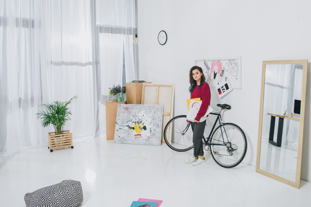 Pretty lady holding sketches and standing by bicycle
