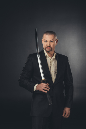 man in suit with katana sword looking at camera on black 写真素材