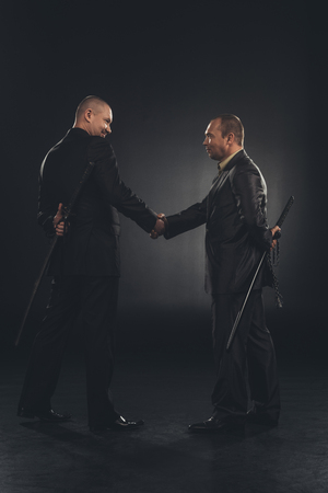 side view of yakuza members shaking hands with katanas behind back isolated on black Stock Photo