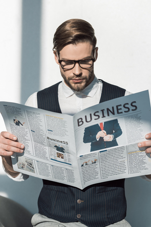 portrait of stylish young businessman in eyeglasses reading newspaper Banque d'images