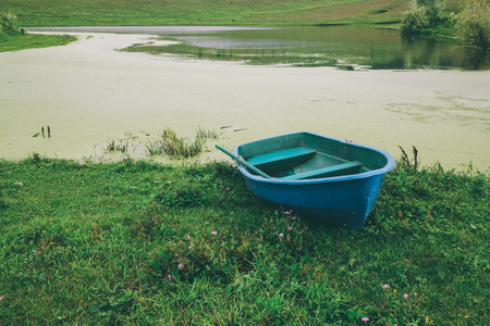 blue boat on green grass near beautiful river in Altai, Russia Stock Photo