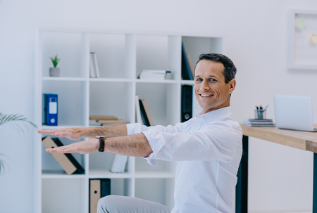 happy mature businessman doing squats at office Stock Photo