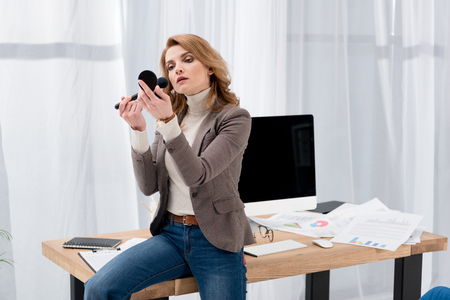 stylish businesswoman looking at mirror while applying makeup at workplace in office