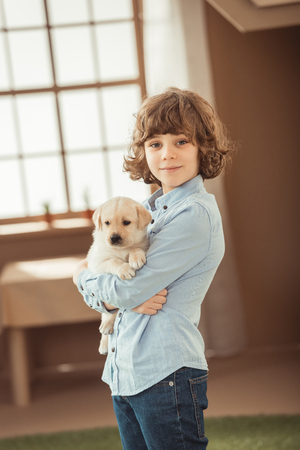 little kid holding his adorable labrador puppy Stok Fotoğraf - 114324996