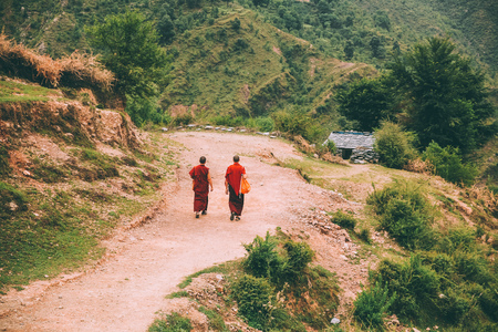 back view of two monks walking on mountain road in Indian Himalayas, Dharamsala, Baksu Banco de Imagens