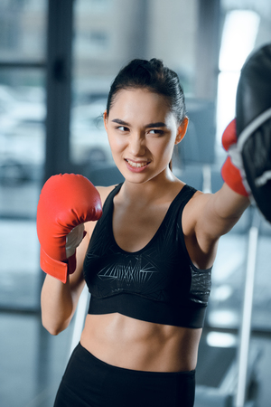 expressive young female boxer training at gym