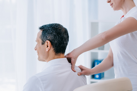 masseuse doing seated shoulder massage for businessman