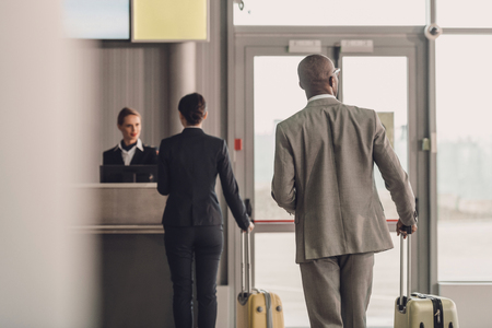 rear view of businesspeople walking to airport check in counter