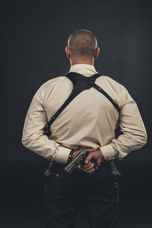 back view of mafia member in shirt holding gun behind back