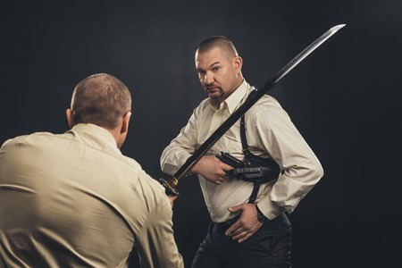 mafia members fighting with gun and katana sword on black Reklamní fotografie