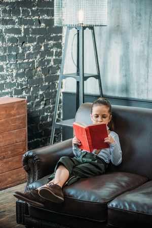 concentrated little child reading book on couch at home Imagens - 114325304