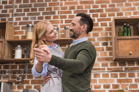 smiling wife and husband dancing on kitchen