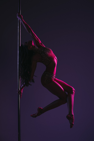 side view of athletic flexible girl exercising with pole on blue Standard-Bild