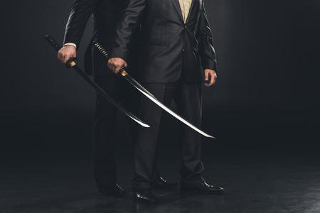 cropped shot of yakuza members with katana swords isolated on black Stok Fotoğraf