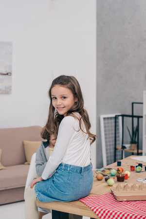 little child sitting on table at home with easter eggs on it