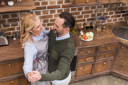 overhead view of smiling wife and husband dancing on kitchen Stock Photo