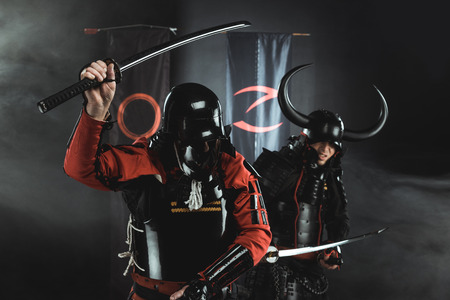 armored samurai fighting with katana swords in front of clan symbols on flags