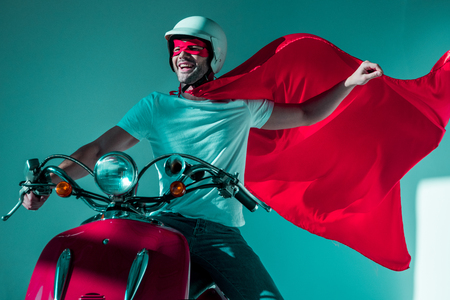 portrait of happy man in protective helmet and superhero costume riding red scooter 版權商用圖片