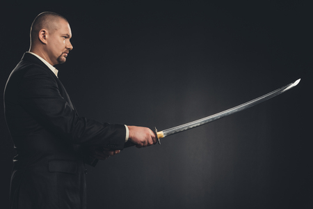 side view of man in suit with katana sword isolated on black 写真素材