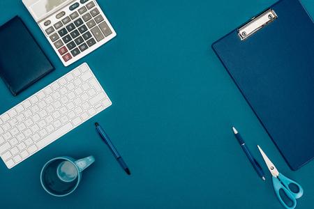 bovenaanzicht van klembord, rekenmachine en kantoorbenodigdheden op blauw Stockfoto