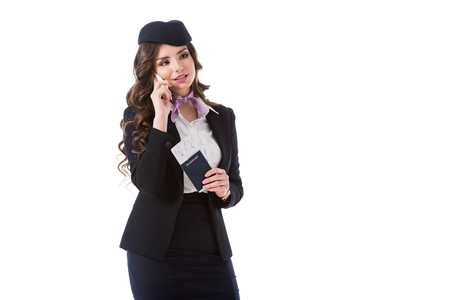 beautiful stewardess talking by smartphone and holding passport with tickets isolated on white Foto de archivo