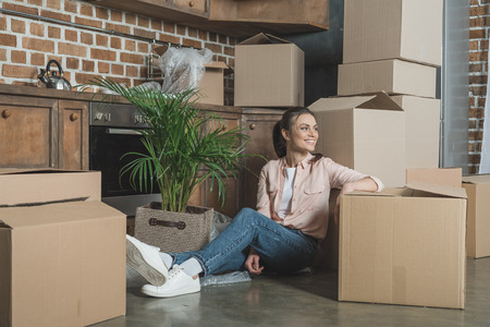 happy young woman smiling and looking away while sitting with cardboard boxes in new apartment Stockfoto